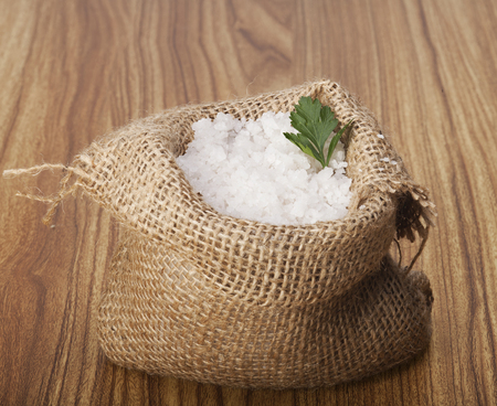 gunny: Sea salt in a jute sack on a wooden . Stock Photo