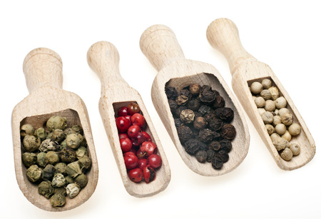 Four different kinds of peppercorns in wooden spoons on a white  photo