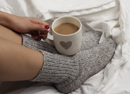 hot girl legs: A cup of coffee or hot chocolate and female feet with socks on a white sheets  Stock Photo
