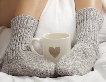 A cup of coffee or hot chocolate and female feet with socks on a white sheets  Banco de Imagens