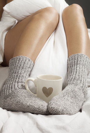 A cup of coffee or hot chocolate and female feet with socks on a white sheets  Standard-Bild