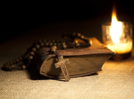 Old Holy Bible, Rosary Beads and Candle. Stock Photo
