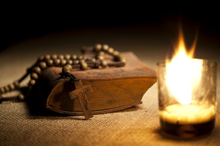 simbol: Old Holy Bible, Rosary Beads and Candle. Stock Photo