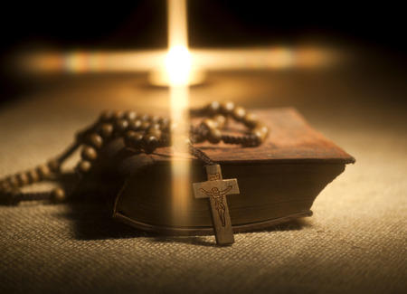 christian background: Old Holy Bible, Rosary Beads and Candle. Stock Photo