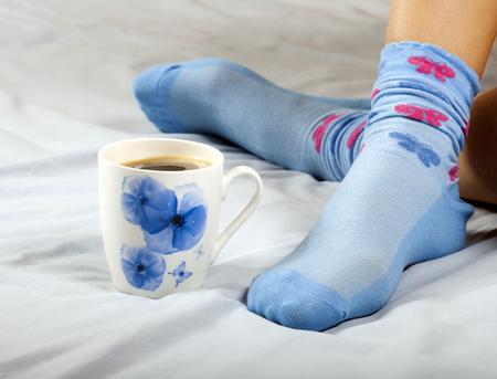 Eine Tasse Kaffee oder heiße Schokolade und weibliche Füße mit Socken auf einem blauen Blatt.