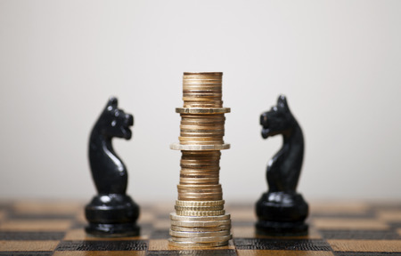 intelligent partnership: Euro coins stacked like a king on a chess board Stock Photo