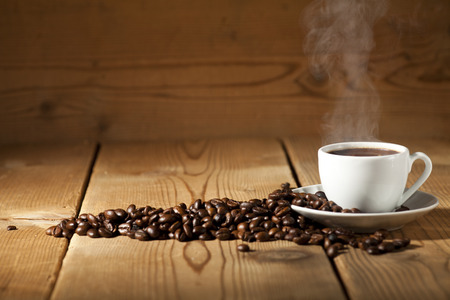 White coffee cup and coffee beans on old wooden background.