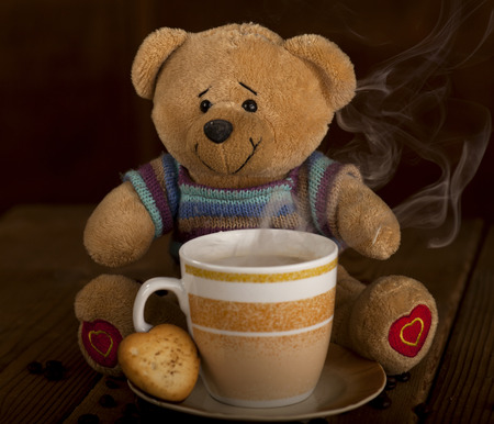 Sweet Teddy bear with cup of coffee, hot chocolate or tea and cookie in heart shape on brown wooden background. photo