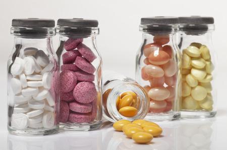 Pills in different colors in glass medicine vials. Macro photo