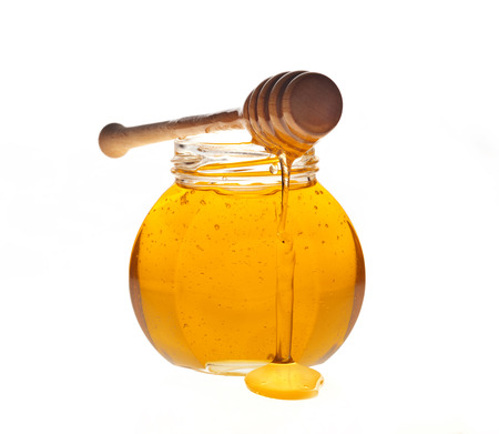 Glass jar of honey with wooden drizzler on a white