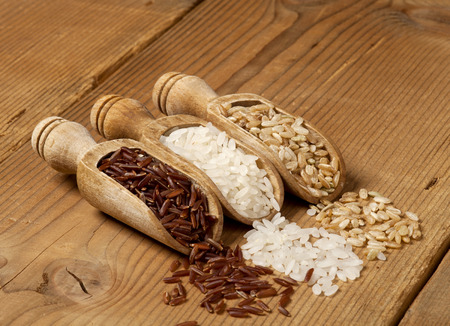 Wooden scoops with different rice types scattered  photo