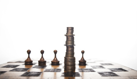 intelligent partnership: Euro or dollar coins stacked like a king on a chess board on a white background. Stock Photo