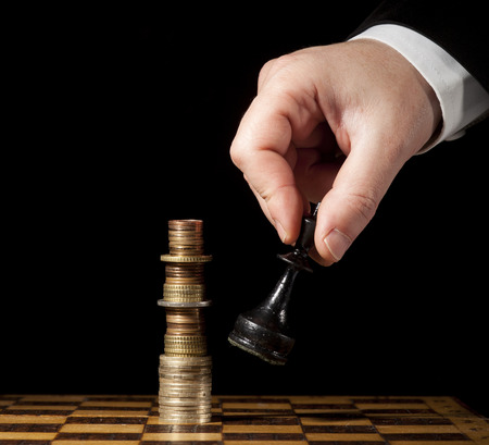 intelligent partnership: Euro or dollar coins stacked like a king on a chess board and hand with another king that tearing the column down. On a black background.