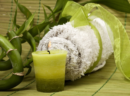 Spa background with rolled towel, green candle and bamboo on green pad. photo