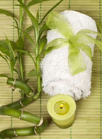 Spa background with rolled towel and green candle with bamboo on green pad. photo