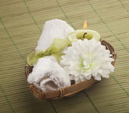 Spa background with rolled towel and green candle with flower in a basket. photo