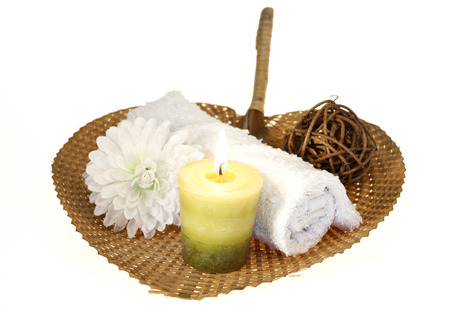 Spa background with rolled towel and green candle with flower on a pad. photo