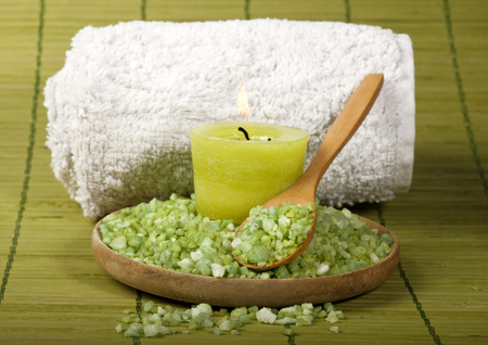 Spa background with sea salt in wooden spoon, rolled towel and candle. photo