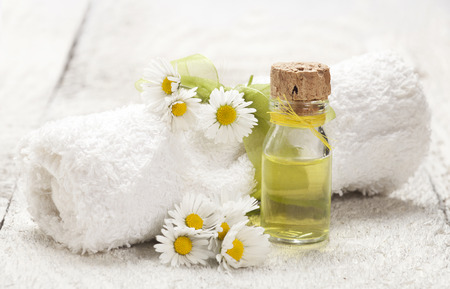Spa background with glass vial with essential oil, rolled towel and chamomile on old wooden background.