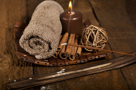 Spa background with rolled towel, candle, sticks of cinnamon and incense stick. photo