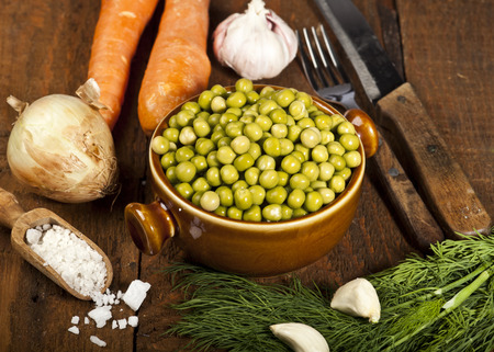 Green peas in a bowl on wooden background. photo