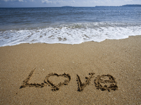 evoking: Love text drawn on the sand of a beach