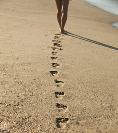 Young woman walking alone on the sand beach in the sunset and leave footprints behind. Focus on the steps in the sand.