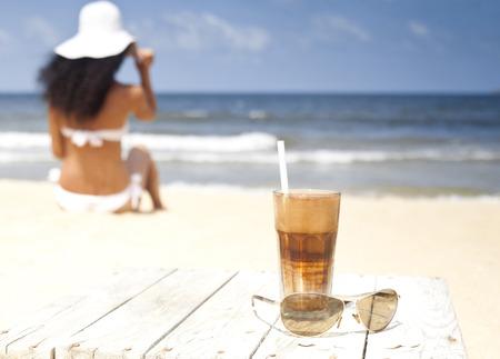 해변에 나무 테이블에 커피와 안경을 아이스. swinsuit와 모자 바다 시청 거리의 여자.