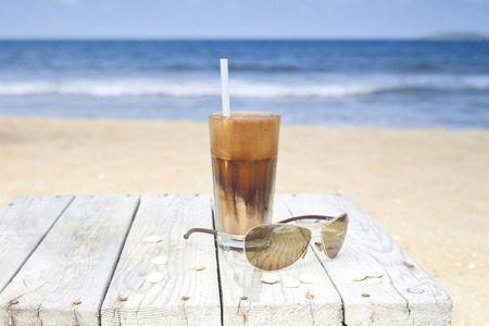 Iced coffee and glasses on a wooden table on the beach.