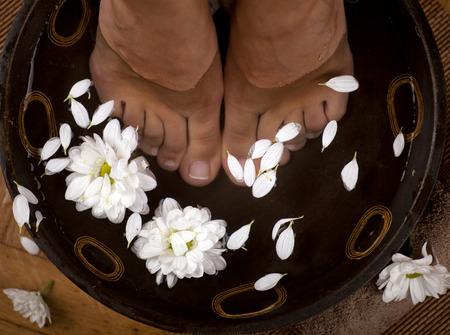 꽃과 수건 발 스파 그릇에 여성의 발