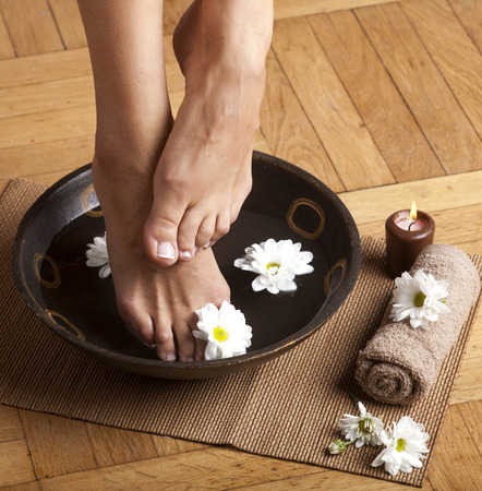 Feminine feet in foot spa bowl with flowers, towel and candle.