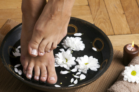 to soak: Feminine feet in foot spa bowl with flowers, towel and candle.
