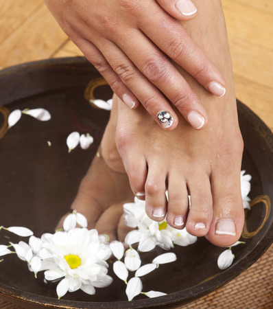 Feminine feet in foot spa bowl with flowers and hand photo