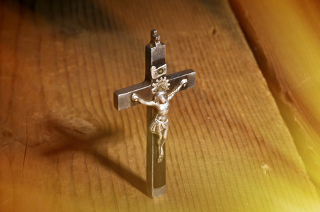 psalm: Old metal and wooden Crucifix with shadow on wooden background. Stock Photo