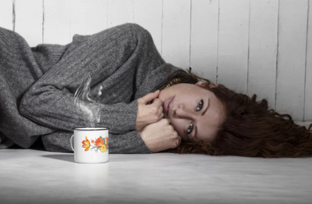 Beautiful melancholic girl lying on the floor with cup of coffe, hot chocolate or tea. photo