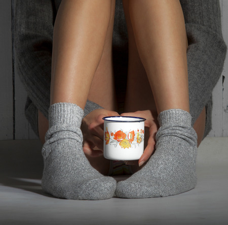 old macro: Girl with warm socks and sweater sitting on the floor with cup of coffee, hot chocolate or tea. Stock Photo