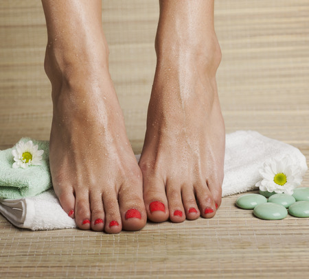 Female feet with drops of water, towel, flowers and spa rocks. Standard-Bild