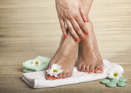 Female feet and hand with drops of water, towel, flowers and spa rocks. Copy space.