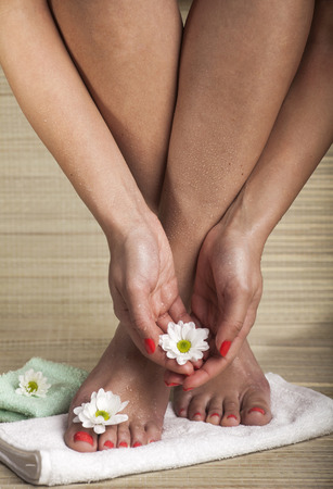 easing: Female feet and hands with drops of water, towel and flowers. Copy space.