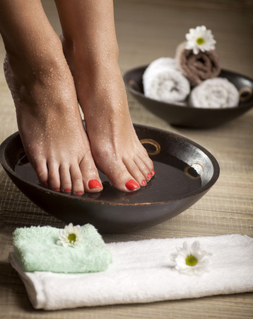 Female feet with drops of water, spa bowls, towels and flowers.