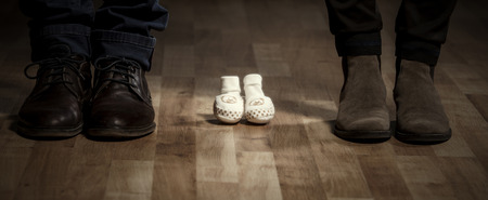 Parents waiting for a baby. Mother and father with elegant shoes and baby shoes between them.