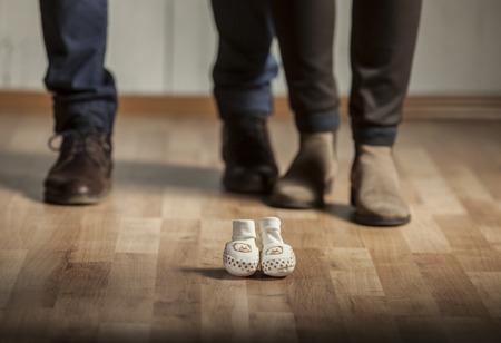 Die Eltern warten auf ein Baby. Mutter und Vater mit elegante Schuhe und Babyschuhe vor ihnen.