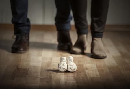 nato: I genitori in attesa di un bambino. Madre e padre con le scarpe eleganti e scarpe per bambini di fronte a loro.