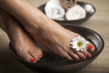 pedicura: Pies femeninos con gotas de agua, cuencos de spa, toallas y flores.