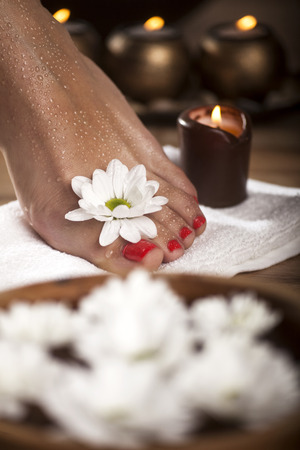 rejuvenate: Female feet with drops of water, spa bowls, towels, flowers and candles.