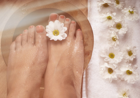 Female feet with drops of water, spa bowl, towel and flowers
