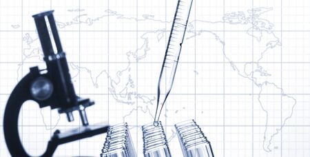 world technology: Closeup of glass test tubes and laboratory microscope on a world map background. Stock Photo
