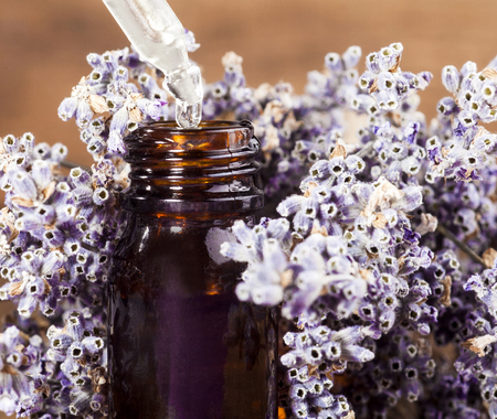 exfoliate: Spa background with bunch of lavender and glass vial with essential oil.