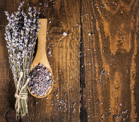 medical herbs: Spa background with bunch of lavender and wooden scoop with sea salt.