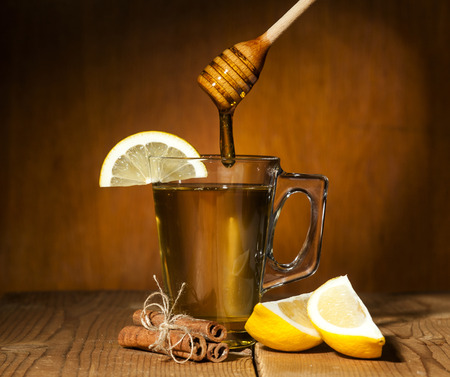 Transparent cup of tea with honey, cinnamon and lemon on wooden background.